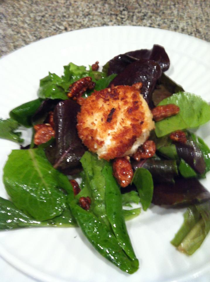 Fried goat cheese medallion on top of mixed greens, with an orange champagne vinaigrette